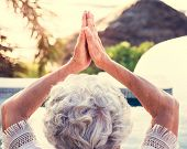Senior adult practicing yoga by the pool poster