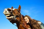 Beautiful girl riding a horse with a sense of humor. Focus is on the muzzle horse