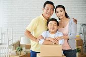 Loving Asian Family Of Three Posing For Photography With Wide Smiles While Distracted From Unpacking poster