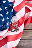American Justice Handcuffs On Flag, Top View. Handcuffs And Usa Flag On Wooden Background. Law And J poster