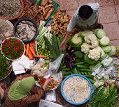 Old muslim woman selling fresh vegetables in traditional asian market.