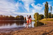 Young Man And Woman Running On Summer River Bank. Happy Couple In Love Having Fun At Sunset. Guys Ch poster