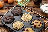 Different Muffins In Bakeware Or Muffin Pan On Broun Wooden Background. Basic Muffin Recipe. Homemad poster