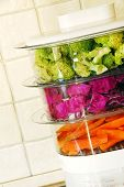 stock photo of kitchen appliance  - green broccoli magenta cabbage and orange carrots in steamer - JPG