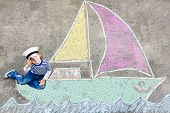 Adorable Little Kid Boy Playing With Colorful Chalks And Painting Ship Or Boat Picture. Creative Lei poster