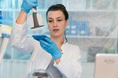 Young woman with genetic research in the laboratory research of cancer diseases poster