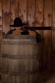 foto of wild west  - A cowboy hiding behind a barrel getting ready to shoot his rifle - JPG