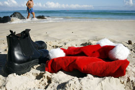 foto of santa claus hat  - Father Christmas on Boxing Day relaxing strolling on the beach after the busiest night of the year showing his hat and the ocean in the background - JPG