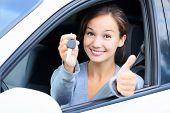 stock photo of car-window  - Happy girl in a car showing a key and thumb up gesture - JPG