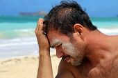 Young Man With Sand On Face By Beach