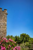 Tower Corner, No Clouds, Blurred Flowers. Beautiful Spring Day And Archeological Ruins At Butrint Na poster