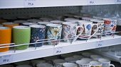 Close Up Of Many Coloured Coffee Or Tea Mugs And Cups On Sale In A Super Market. Many Different Cera poster