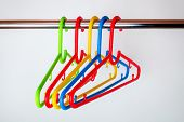 Five Multicolored Plastic Clothes Hangers On A Rod In The Closet. Set Of New Colorful Plastic Clothe poster