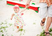 baby girl first steps holding her father hand