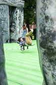 Teenager summersaulting on the life-sized inflatable replica of Stonehenge