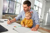 multi-tasking, freelance and fatherhood concept - working father with baby daughter at home office poster
