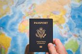 Top View Of Man Holding Usa Passport On World Map Background. Passport Control. A Young Man Is Prepa poster
