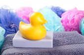 A duck shaped bar of soap resting on a purple bath towel with colorful shower poufs on white.