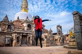 Young Girl Jumps And Dabs At A Sacred Buddhist Monastery. Sculptures Of Gods And Goddesses Carved On poster