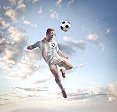 Jogador de futebol, tiro de cabeça uma bola de futebol no céu