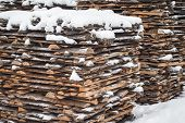 Stack Of Sawn Planks Covered With Snow.a Large Pile Of Boards On The Street Is Covered With Snow. St poster
