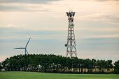 A Wide Angle Late Afternoon View Of A Cell Site Tower In A Lush Green Landscape With Woodland, Grass poster