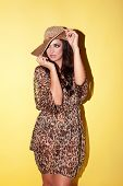 Elegant stylish woman wearing a fashionable animal print outfit with a wide brimmed straw hat