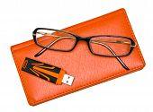 Notebook, óculos e Pendrive isolado no branco