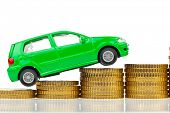 a model car is on coins. rising costs for gasoline car prices, insurance and taxes.