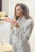 Beautiful woman smelling her perfume