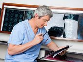 stock photo of radiogram  - Mature male medical professional in uniform reading document at clinic - JPG