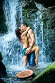 stock photo of waterfalls  - Couple hugging and kissing under waterfall - JPG