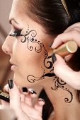 Brunette Having Applied Face Painting By Makeup Artist