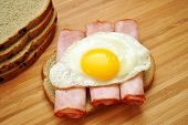 Ham and Egg Sandwich on a Wood Table.