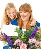 Teenage daughter giving flowers and a card to her mother on Mother's Day.  Card blank ready for your