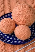 Three ball of pink yarn on a plate with asterisks and spokes for knitting