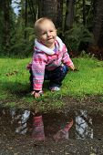 One year old girl outside, playing with a puddle.