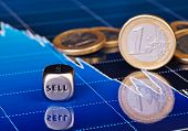 Close-up Dices Cube With The Word Sell, One-euro Coins And Downtrend Financial Chart As Background.