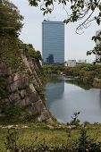 The Moat Of Osaka Castle With Modern Buildings In The Distance