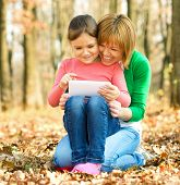 Mother and her daughter is playing with tablet, outdoor shoot
