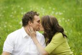 image of kissing couple  - A young attractive couple shares a kiss on a warm summer day