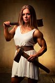 Young woman bodybuilder with hammer and axe. Ancient style.