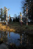 foto of totem pole  - Aboriginal Totem Poles in Stanley Park reflecting in a pond. Vancouver, British Columbia, Canada.