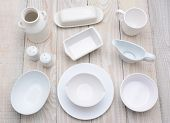High angle shot of different dinnerware items,  of varying shades of white.  Horizontal format on a