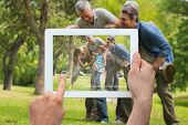 Hand holding tablet pc showing extended family having fun in the park