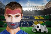 Composite image of serious young russia fan with face paint against large football stadium