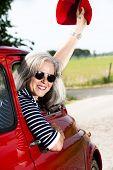 Senior happy woman with vintage car