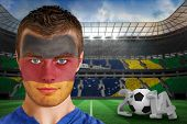 Composite image of serious young german fan with face paint against large football stadium