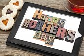 foto of teats  - Happy Mother Day in vintage letterpress wood type on a digital tablet with a cup of tea and heart cookies - JPG