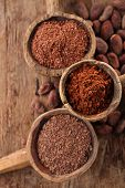 picture of chocolate spoon  - cocoa powder in spoon on roasted cocoa chocolate beans background - JPG